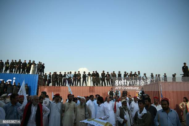 TOPSHOT Pakistani policemen stand guard atop containers blocking a street leading to the Presidential palace during a protest rally by tribesmen in...
