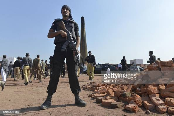Pakistani policemen stand guard during the visit of a members committee investigating the killing of a Christian couple at a brick Kiln in Kot Radha...