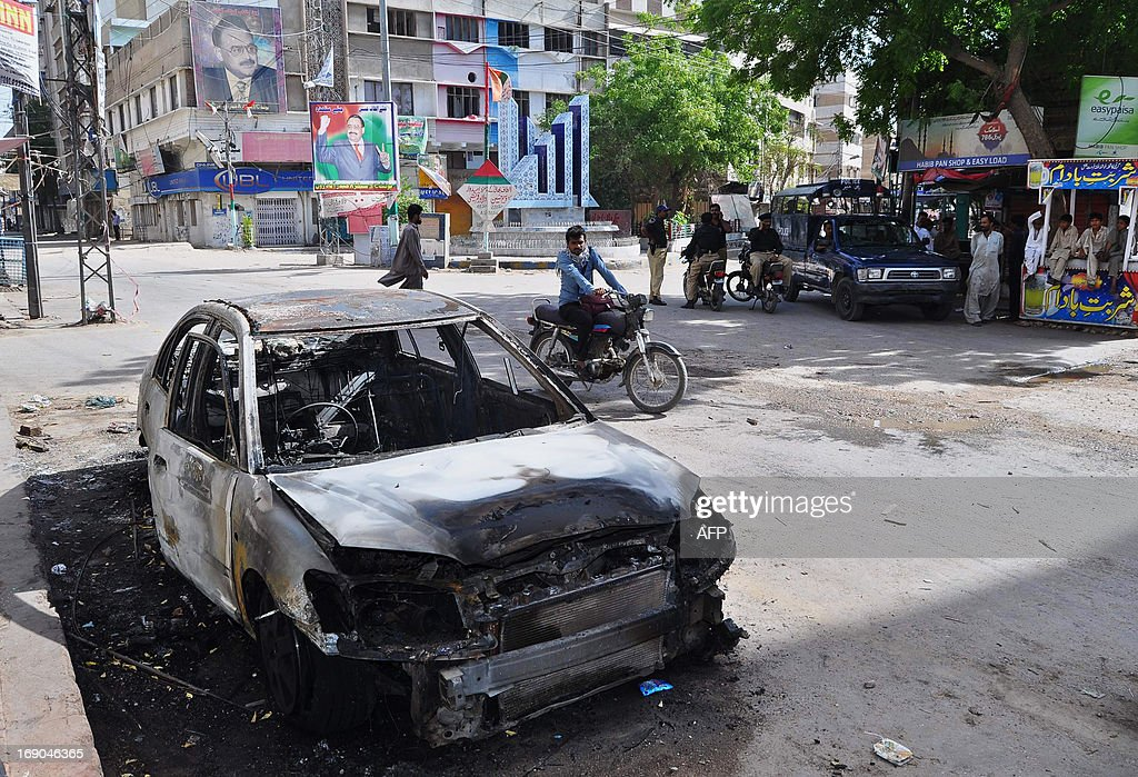 Pakistani policemen stand guard near a burnt vehicle set on fire by protesters demonstrating against Imran Khan in Hyderabad on May 19, 2013. Khan May 19, blamed a rival political leader for the killing of a senior member of his party, who was gunned down outside her home in the violence-plagued city of Karachi on the eve of a partial re-run in the southern city of the May 11 election. AFP PHOTO/ Yousuf NAGORI