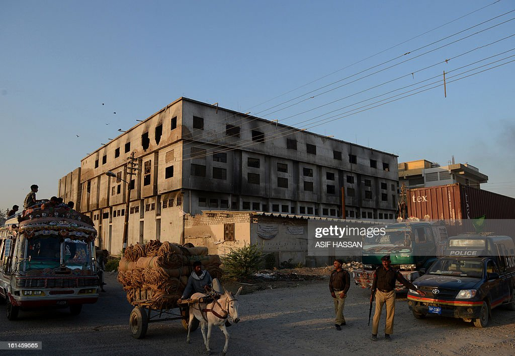 Pakistani policemen stand in front of a burnt out garment factory in Karachi on February 11, 2013. Pakistani police have moved to drop murder charges against the owners of a garment factory where 289 workers were killed in a fire in 2012, the mens' lawyer said. AFP PHOTO/Asif HASSAN