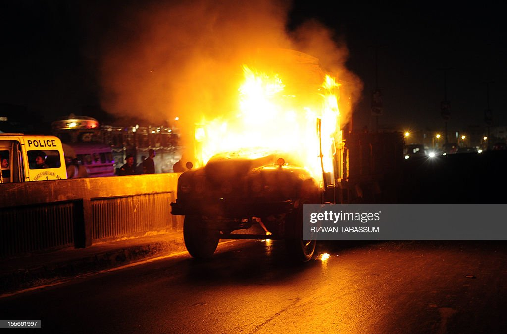 Pakistani policemen stand near a burning truck torched by an angry mob following sectarian killing in Karachi on November 6, 2012. Gunmen shot dead three Shiite Muslims and wounded two others on Tuesday in a fresh sectarian attack in Pakistan's troubled southwestern province of Baluchistan, police said.