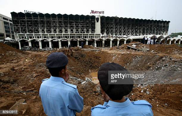 Pakistani policemen stand next to a crater left by a bomb blast next to the Marriott Hotel in Islamabad on September 22 2008 two days after a suicide...