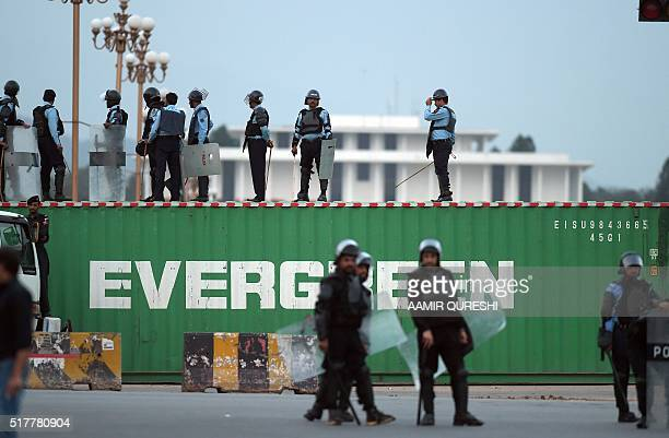 Pakistani policemen stand on the top of a shipping container placed on a road to block acces for supporters of executed Islamist Mumtaz Qadri...
