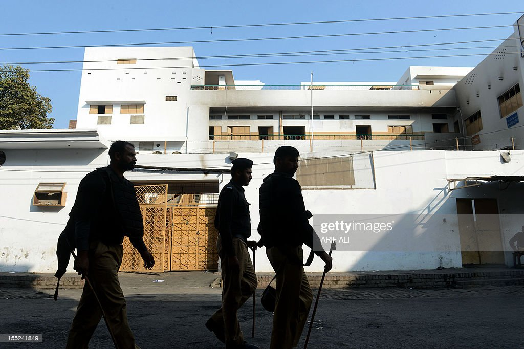Pakistani policemen walk past Farooqi Girls' High School that was set fire by an angry mob, following a protest alleging the school gave a test that insulted the Prophet Mohammed, in Lahore on November 2, 2012. A Pakistani teacher at the centre of a blasphemy row was in hiding Friday as her school management denied all responsibility for the 'dirty act' and called for her to be punished. Arfa Iftikhar was forced into hiding after a furious mob stormed Farooqi Girls' High School in the eastern city of Lahore over a piece of homework she set that allegedly contained derogatory references to the Muslim prophet Mohammad.