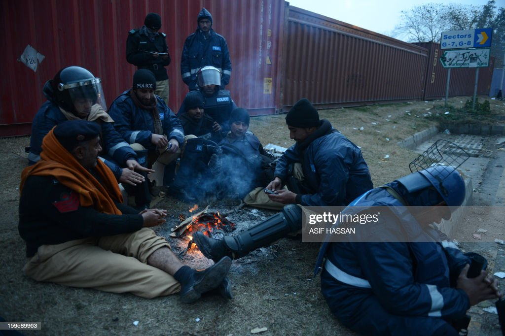 Pakistani policemen warm themselves around a fire on the fourth day of protests in Islamabad on January 17, 2013. Pakistan's president on January 16 intervened to stop authorities from using force against protesters who are calling for parliament to be dissolved in Islamabad's largest political rally in years. AFP PHOTO / Asif HASSAN