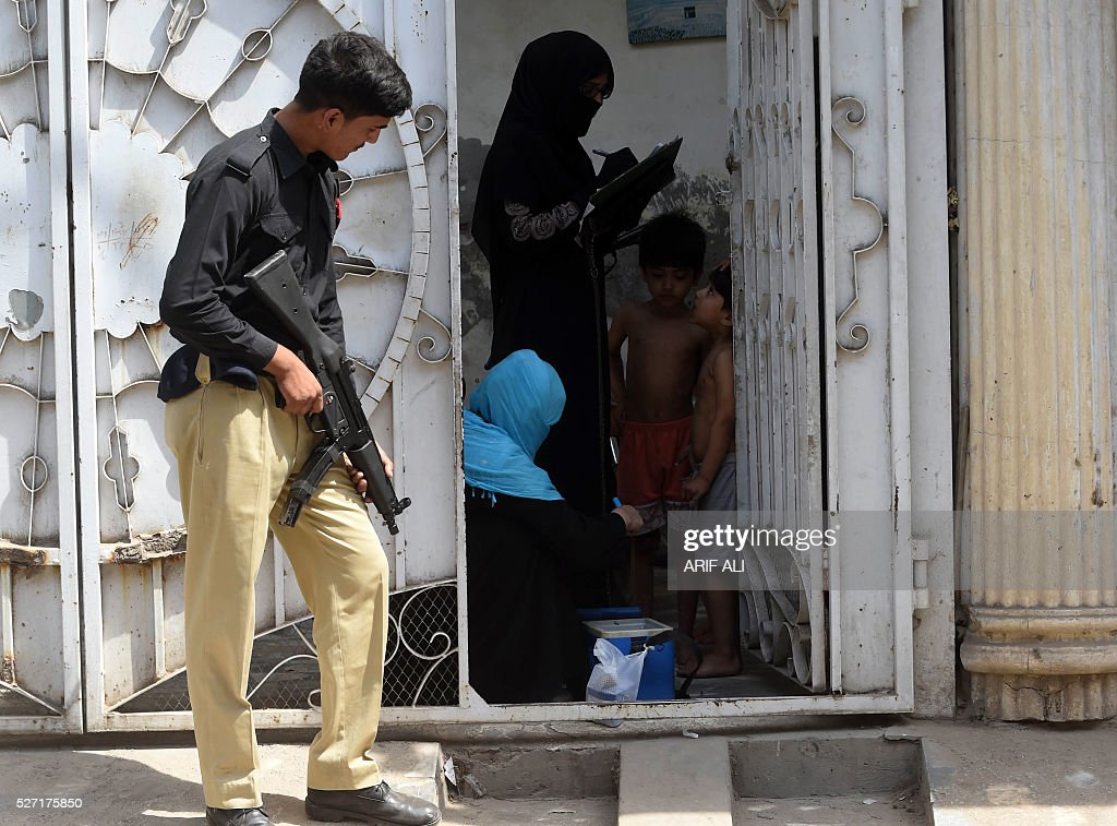 A Pakistani policman stands guard over polio health workers during a door-to-door polio campaign in Lahore on May 2, 2016. Pakistan is one of only three countries in the world where polio remains endemic but years of efforts to stamp it out have been badly hit by reluctance from parents, opposition from militants and attacks on immunisation teams. / AFP / ARIF ALI