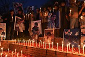 Pakistani political party workers traders and students light candles during a vigil in Islamabad on December 18 for the children and teachers killed...