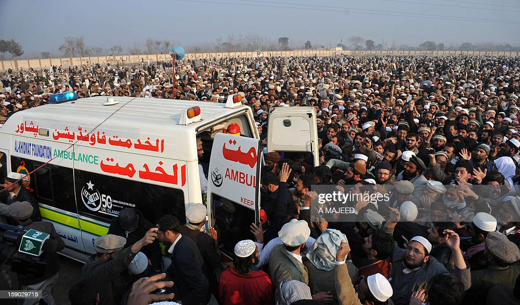 Pakistani politicians and supporters gather around an ambulance carrying the coffin of former Jamaat-i-Islami (JI) chief and politician Qazi Hussain Ahmed after his funeral prayers in Peshawar on January 6, 2013. Ahmed (74), a prominent religious scholar remained a strong critic of counter-terrorism policy of the United States, and was widely known for his opposition of the United States participation in the war in neighboring Afghanistan.