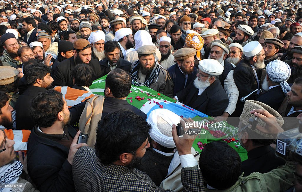 Pakistani politicians and supporters gather around the coffin of former Jamaat-i-Islami (JI) chief and politician Qazi Hussain Ahmed after his funeral prayers in Peshawar on January 6, 2013. Ahmed (74), a prominent religious scholar remained a strong critic of counter-terrorism policy of the United States, and was widely known for his opposition of the United States participation in the war in neighboring Afghanistan.