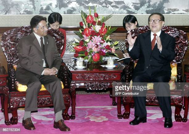 Pakistani President Gen Pervez Musharraf left listening to former Chinese President Jiang Zemin who is chairman of the commission that runs China's...