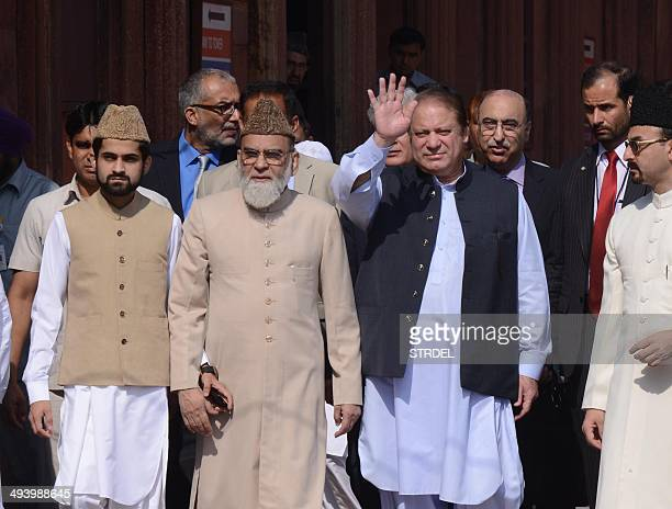 Pakistani Prime Minister Nawaz Sharif waves as he walks with Syed Ahmed Bukhari the Shahi Imam of the 17th century Jama Masjid during his visit to...