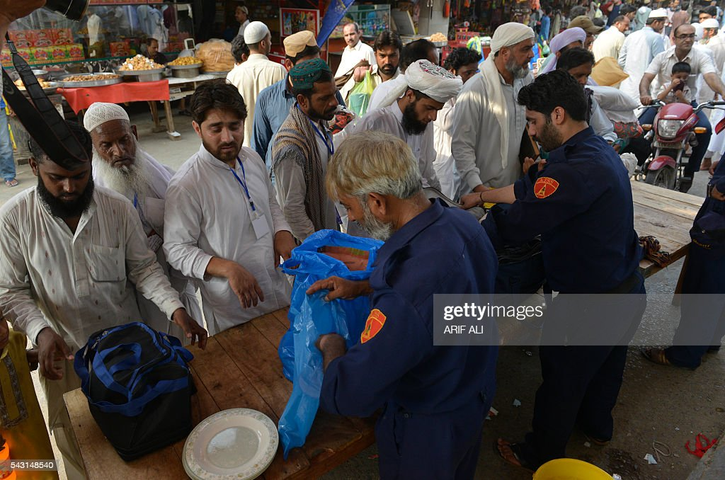 Pakistani private security personnel check the belonging of Muslims before entering a mosque on the start of Itikaf in Lahore on June 26, 2016. Itikaf is a spiritual retreat in a mosque for men, usually held during the last 10 days of Ramadan and during which Muslims spend the evening and night in the mosque devoting their time to solitary prayers and reading the Koran. / AFP / ARIF ALI