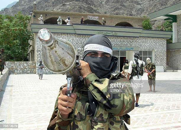 A Pakistani proTaliban militant carries rocket propelled granade launcher as he stands inside the shrine in Lakaro village in the lawless Mohmand...