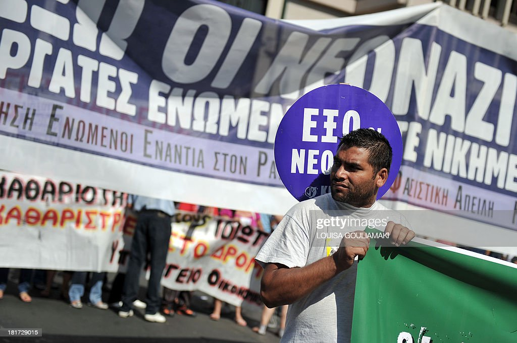 A Pakistani protester stands on September 24, 2013 in front of a banner, reading: ' Neo Nazi Out,' during a demonstration in Athens. The fatal stabbing of 34-year-old hip hop artist Pavlos Fyssas on September 18 touched off street protests and prompted authorities to take a harder stance against the neo-Nazi party, Golden Dawn. Two top Greek police chiefs quit in a shake-up on on September 23 after the murder of the anti-fascist musician by an alleged member of Golden Dawn sparked protests, and led to a probe of a possible police connection. AFP PHOTO/ LOUISA GOULIAMAKI