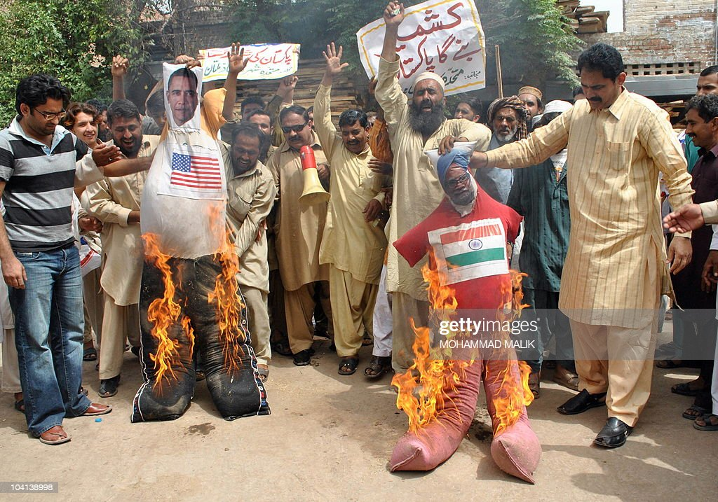 Pakistani protesters hold burning effigies of US President Barack Obama and Indian Prime Minister Manmohan Singh during an antiIndian protest in...