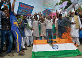 Pakistani protesters shout slogans and burn the Indian national flag during a demonstration against against violence in Indianadministered Kashmir in...