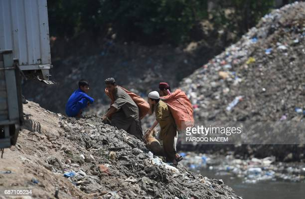 Pakistani ragpickers search for recyclable items in Rawalpindi on May 23 2017 / AFP PHOTO / FAROOQ NAEEM