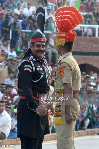 A Pakistani Ranger and Indian Border Security Force official shake hands during the daily beating of the retreat ceremony at the IndiaPakistan Wagah...