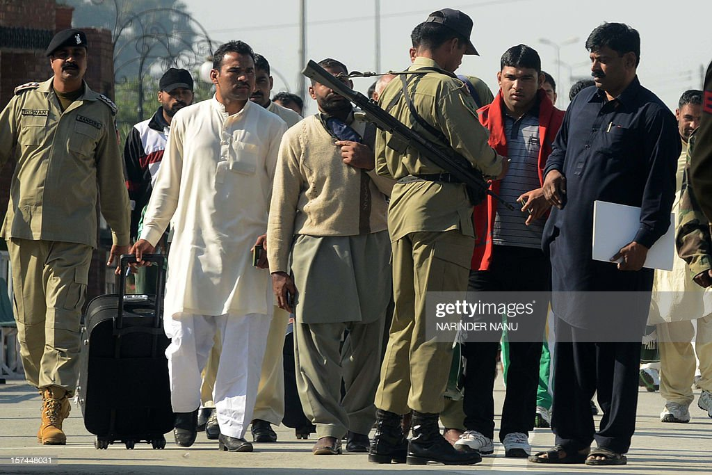 A Pakistani Ranger (3R) checks the documents of Pakistani kabaddi team players prior to their crossing the India-Pakistan Wagah Border on December 3, 2012. The 16-member Pakistani team along with team captain Musharraf Javed, arrived in India to play in the 3rd Kabaddi World Cup 2012 tournament in Hoshiarpur which runs from December 1-15.