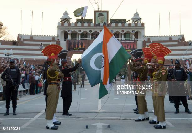 Pakistani Rangers and Indian Border Security Force personnel fold their respective national flags as they perform during the daily beating of the...