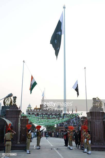 Pakistani Rangers and Indian Border Security Force personnel perform the flag off ceremony during the daily beating of the retreat ceremony at the...