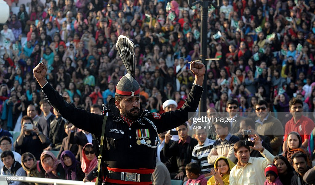 Pakistani Rangers perform the 'flag off' ceremony with unseen Indian Border Security Force personnel at the Pakistan-India Wagah Border Post on January 15, 2013. Indian Prime Minister Manmohan Singh warned Tuesday that there 'cannot be business as usual' with neighbouring Pakistan after last week's deadly flare-up along the border in disputed Kashmir. AFP PHOTO/Arif ALI
