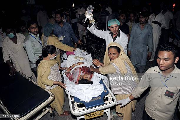 Pakistani relatives and emergency workers carry an injured woman to the hospital in Lahore on March 27 after at least 56 people were killed and more...