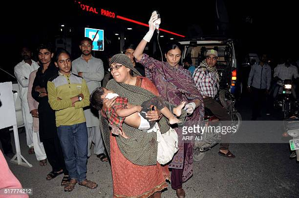 Pakistani relatives bring an injured child to the hospital in Lahore on March 27 after at least 56 people were killed and more than 200 injured when...
