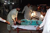 Pakistani relatives brings an injured woman to the hospital in Lahore on March 27 after at least 56 people were killed and more than 200 injured when...