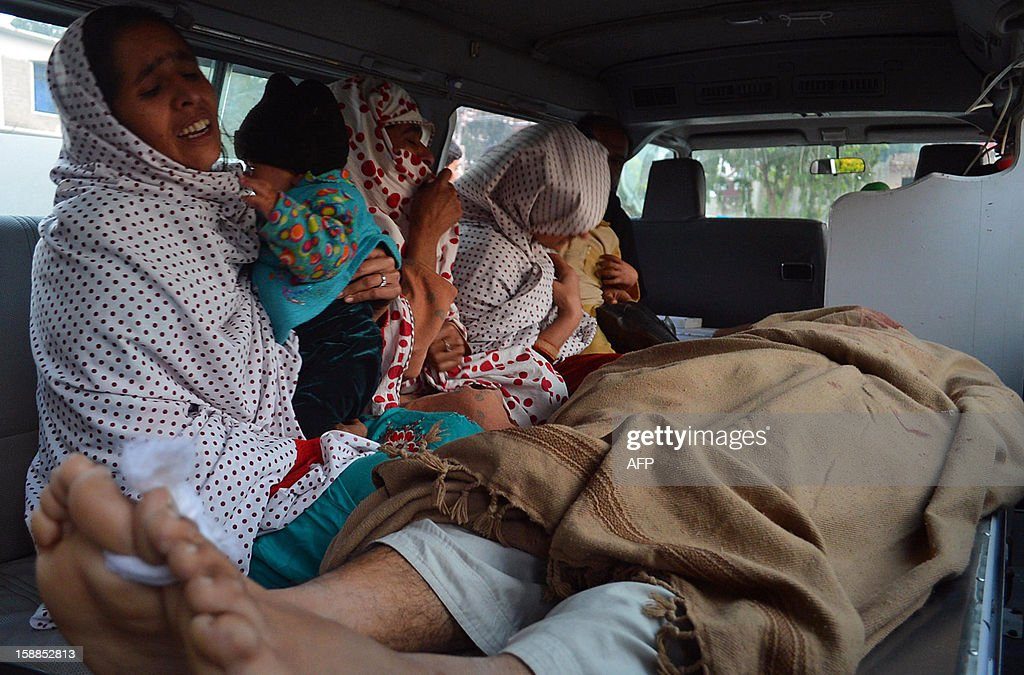 Pakistani relatives mourn next to a body of a charity worker following an attack by gunmen in Swabi on January 1, 2013. Six women and a man working for a Pakistani health and education charity involved in vaccinations were shot dead on their way home from a community centre, officials said.