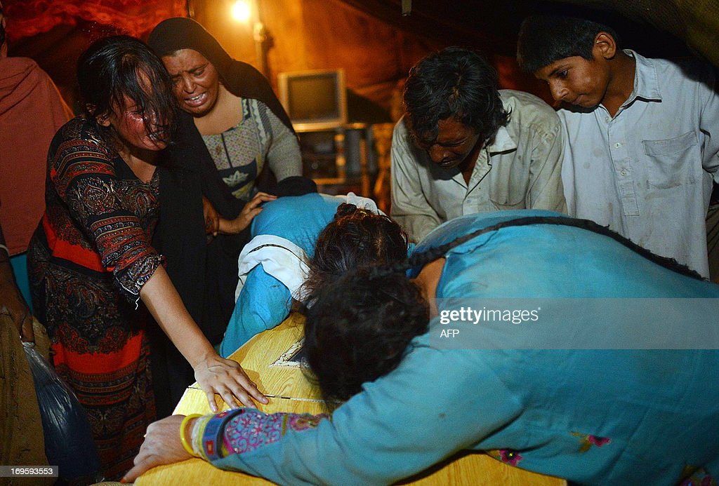 Pakistani relatives mourn over the coffin of a blast victim following a bomb explosion in Peshawar on May 28, 2013. Two people were killed and about a dozen wounded when a motorbike bomb exploded in northwest Pakistan late on May 28, police and hospital officials said. AFP PHOTO / A. MAJEED