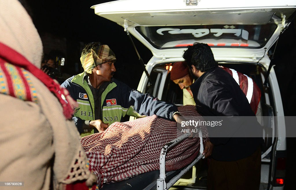 Pakistani relatives move the dead body of drug addict from a hospital in Gujranwala on December 29, 2012. At least 24 people, mostly drug addicts seeking a fix, have died after drinking toxic cough syrup in an eastern Pakistani city, officials said. AFP PHOTO/ Arif ALI
