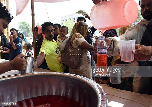 Pakistani relatives of heatstroke victims receive sweet drinks outside a government hospital in Karachi on June 27 2015 More than 1000 people have...