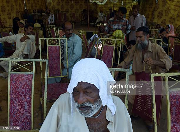 Pakistani relatives of heatstroke victims shelter at a tent outside a government hospital in Karachi on June 27 2015 More than 1000 people have died...