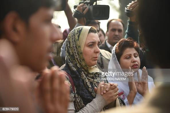 Pakistani relatives of the victim of a plane crash offers prayers at the Pakistan Institute of Medical Sciences hospital in Islamabad on December 8...