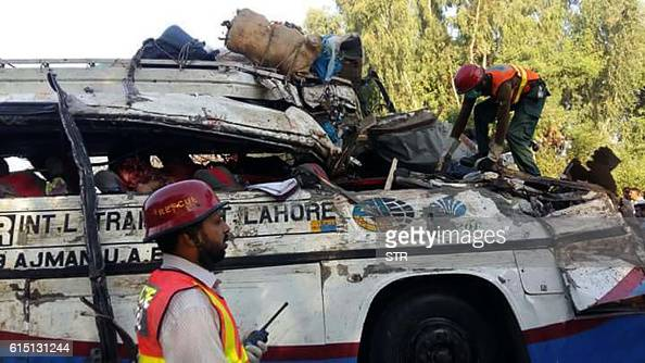 Pakistani rescue officials gather around the wreckage of a passenger bus after an accident in Khanpur some 800 kilometres south of Islamabad At least...