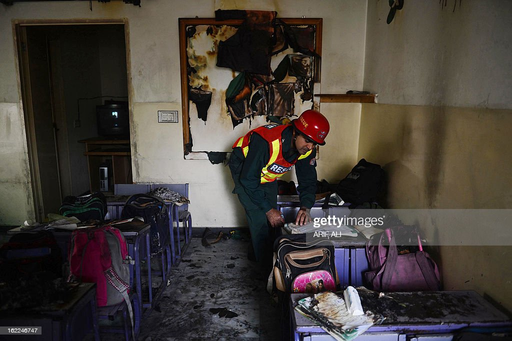 A Pakistani rescue serviceman inspects a classroom which caught fire from a gas leakage in Lahore on February 21, 2013. Over 21 children and a teacher were treated for burn injuries when a fire broke out in a school classroom in Lahore. AFP PHOTO/Arif ALI
