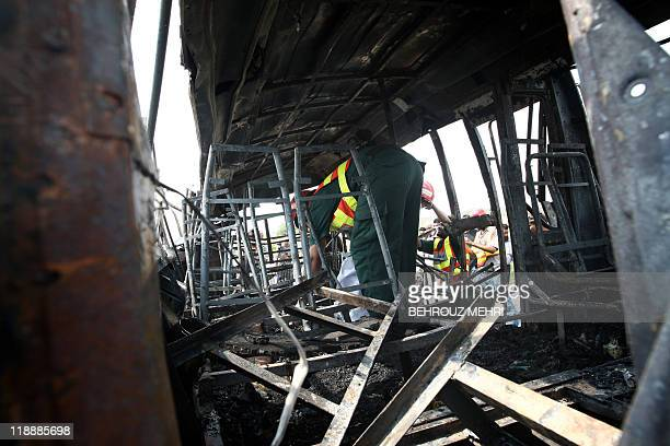 A Pakistani rescue team member collects evidence from inside a burnt bus after the compressed natural gas cylinders powering it exploded while it was...