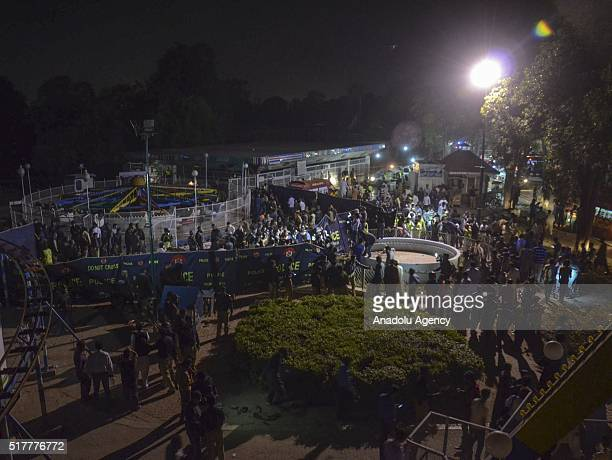 Pakistani rescue workers and police gather at a site after a suicide bomber blew himself up in a crowded park in Lahore killing at least 56 people...