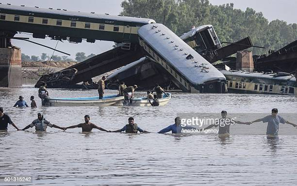 Pakistani rescue workers and troops search the dead body of train victims after it derailed into a canal in Wazirabad in the Punjab province on July...