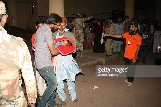Pakistani rescue workers and volunteers unload an injured victim of bomb blast from an ambulance upon his arrival at a local hospital in Hub town...