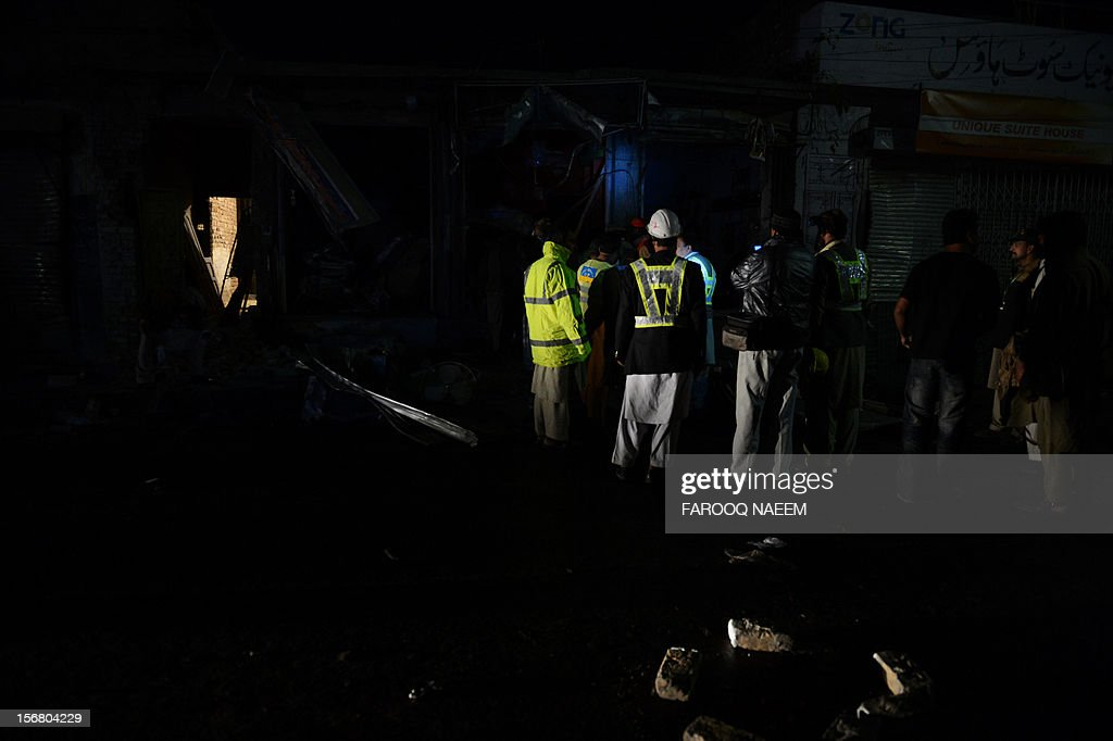 Pakistani rescuers and policemen collect evidence at the bomb blast site in Rawalpindi on November 22, 2012. A blast during a religious procession on Wednesday left at least six people dead and several others injured in the city of Rawalpindi in an attack by a suicide bomber, police said. AFP PHOTO/Farooq NAEEM