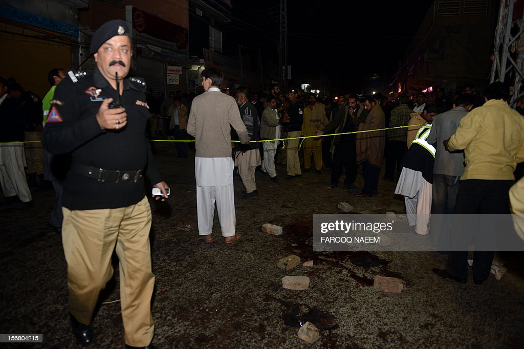 Pakistani rescuers and policemen gather at the bomb blast site in Rawalpindi on November 22, 2012. A blast during a religious procession on Wednesday left at least six people dead and several others injured in the city of Rawalpindi in an attack by a suicide bomber, police said. AFP PHOTO/Farooq NAEEM