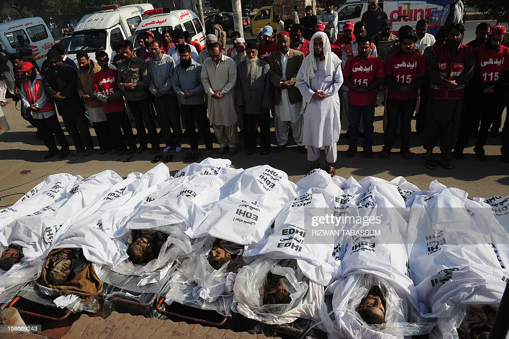 Pakistani rescuers and relatives offer prayers to the dead bodies of illegal immigrants who were lined up for identification who were killed near the border with Iran, in Karachi on December 23, 2012. Unknown gunmen killed 11 people as they prepared to illegally leave Pakistan in the southwestern province of Baluchistan, officials said. AFP PHOTO/Rizwan TABASSUM