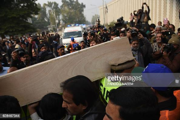 Pakistani rescuers carry the body of a plane crash victim from an ambulance at the Pakistan Institute of Medical Sciences hospital in Islamabad on...