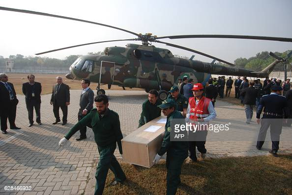 Pakistani rescuers carry the body of a plane crash victim in Islamabad on December 8 after their arrival by helicopter from the crash site in the...