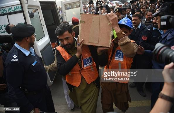 Pakistani rescuers move the body of the victim of a plane crash from an ambulance at the Pakistan Institute of Medical Sciences hospital in Islamabad...