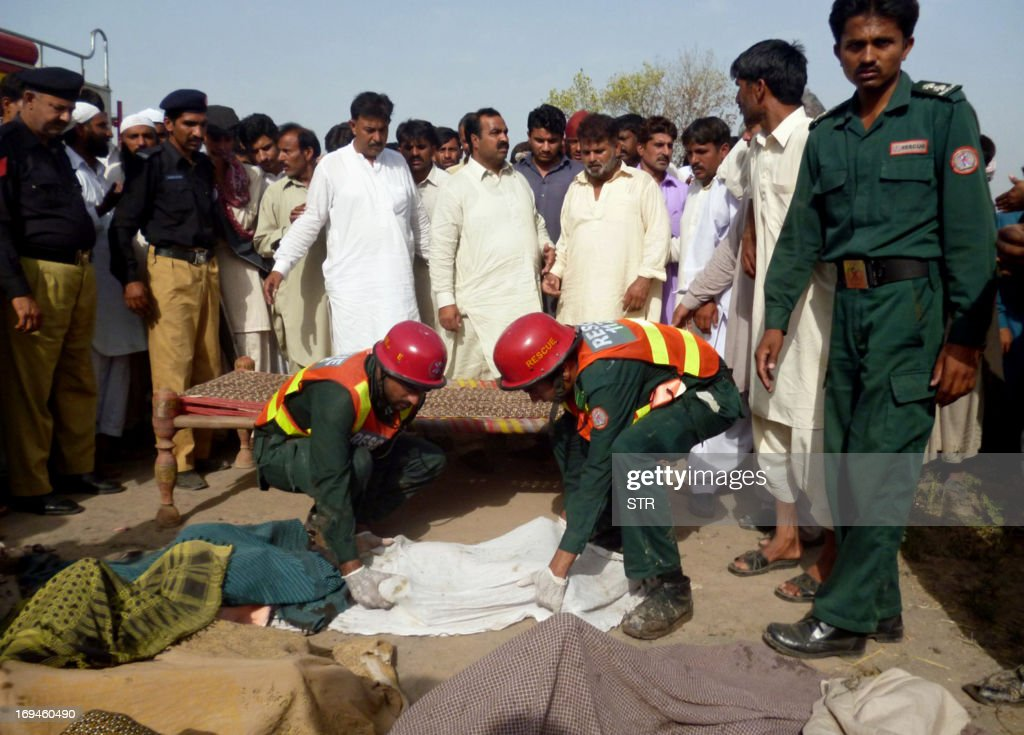 Pakistani rescuers personnel shift dead bodies of school children killed after their school van caught fire in Mangowal, some 185 kilometers from Islamabad on May 25, 2013. Sixteen children and a teacher were killed when their school van caught fire in central Pakistan on Saturday, police said.