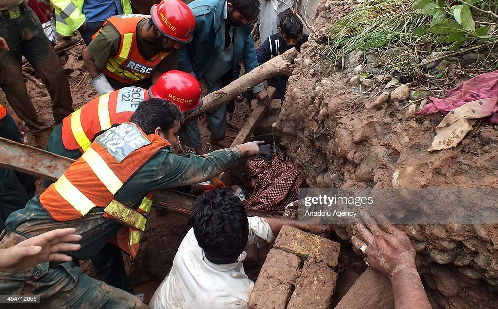 Pakistani rescuers pull out a man trapped under the debris of his collapse house located on the bank of a flooded stream on September 5 2014 in...