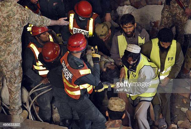 Pakistani rescuers remove a victim from the rubble of a collapsed factory on the outskirts of Lahore on November 4 2015 At least 16 people were...